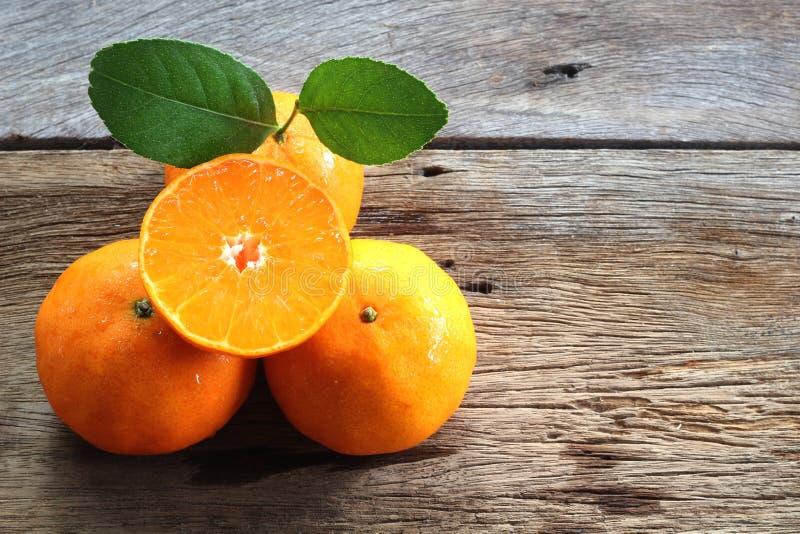 Färska apelsiner och en halv på träplattan royaltyfri fotografi