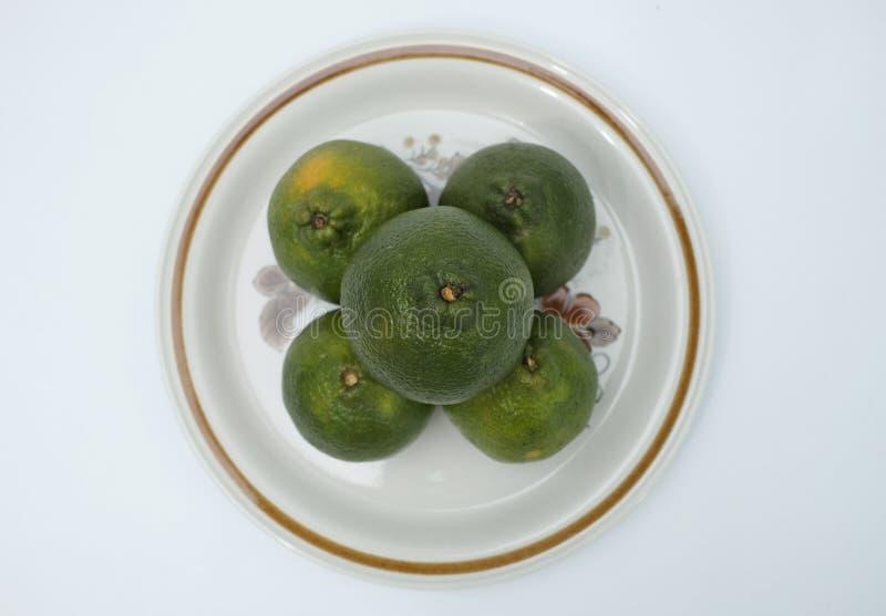Färska och organiska citronfrukter på dekorativ platta royaltyfri bild