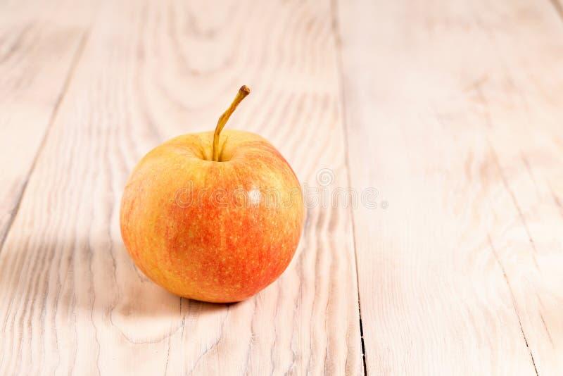 Färska röda äpplen, hela, tillslutna på bondskivor av trä, vega-mat Färskt äpple, gult, moget royaltyfri fotografi
