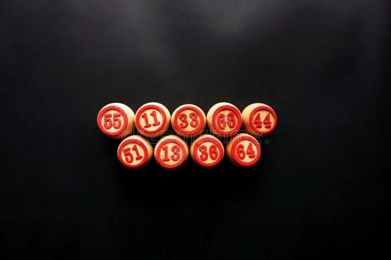 Fässer für ein Brettspiel im Lotto, vereinbart in einer Linie, auf einem schwarzen Hintergrund stockfotografie