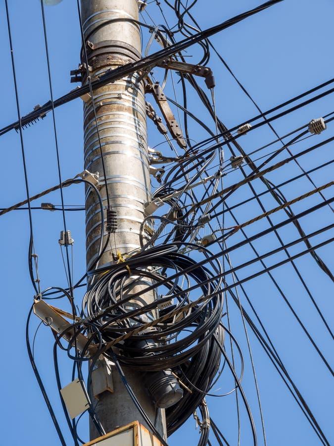Fästande kablar till en konkret pelare i förvirring royaltyfri foto