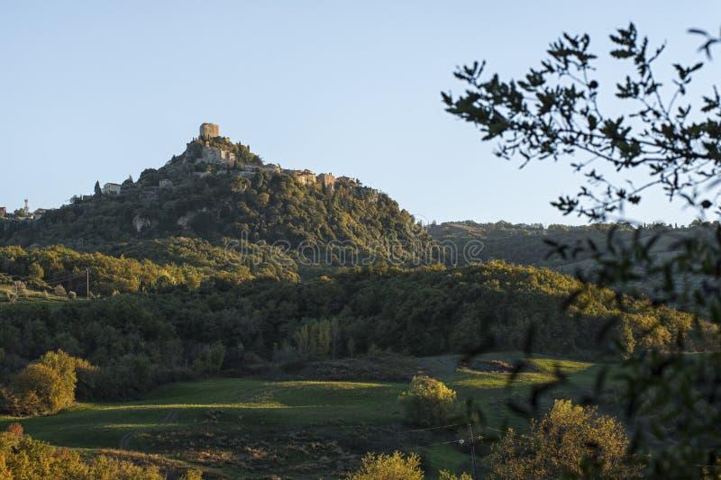 Fästningen av Tentennano ovanför fruktträdgården i en liten liten by i den Castiglione d'Orciaen arkivbilder
