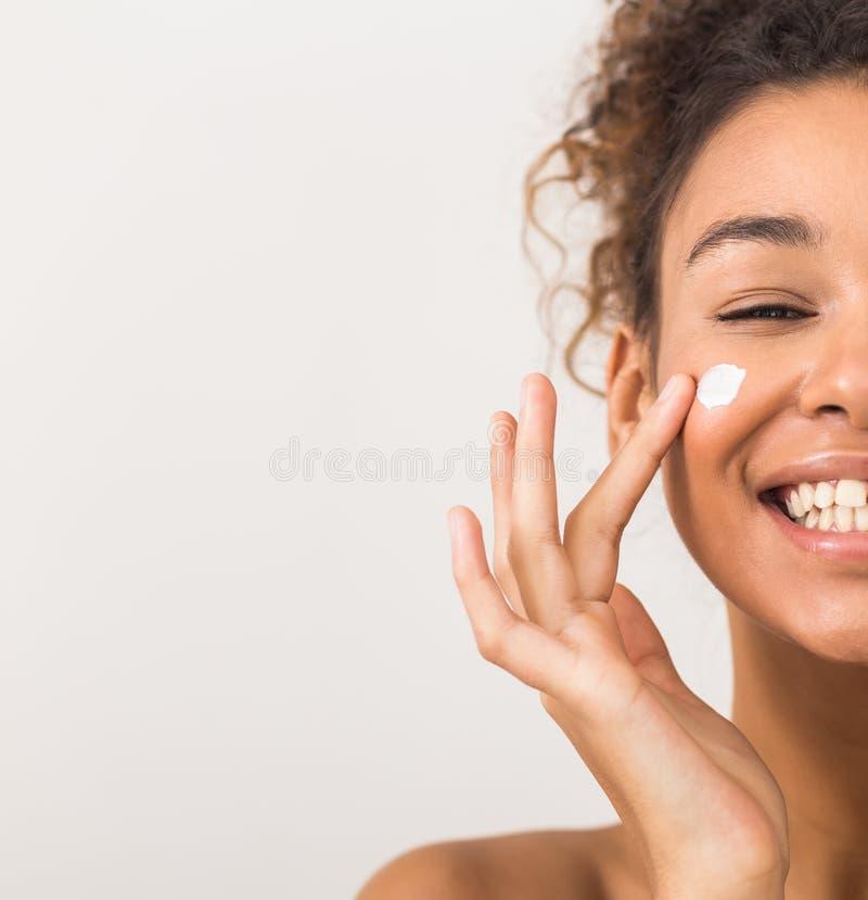 Fästvård Glad svart kvinna som applicerar moisturizer kräm på kinden arkivbild