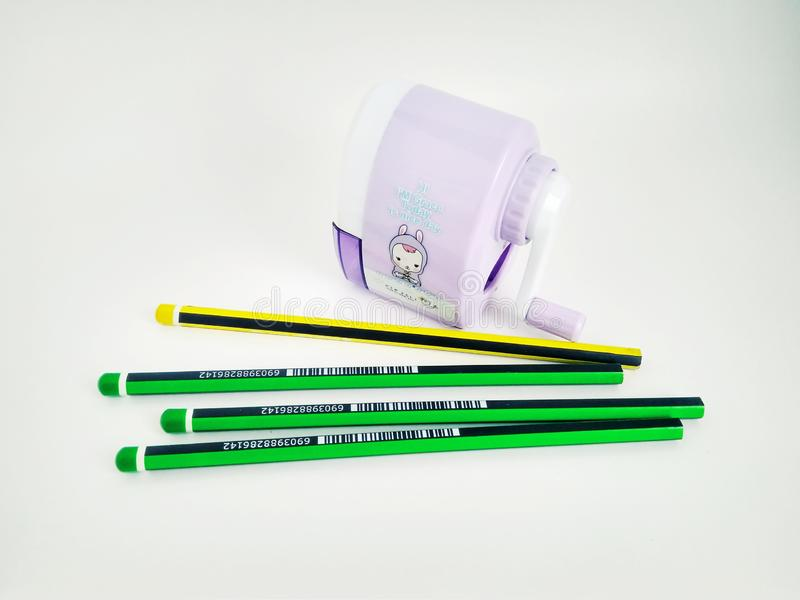 Få blyertspennor och mekanisk vässare på vit royaltyfri foto