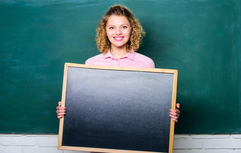 Få dina bästa lösningar lyckligt bräde för mellanrum för studentflickahåll kvinnalärare på svart tavla kopiera avst?nd är här dit royaltyfri bild