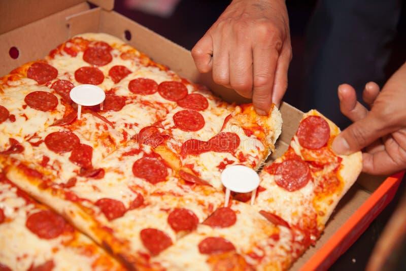 Få en skiva av ny fyrkantig peperonipizza royaltyfri foto