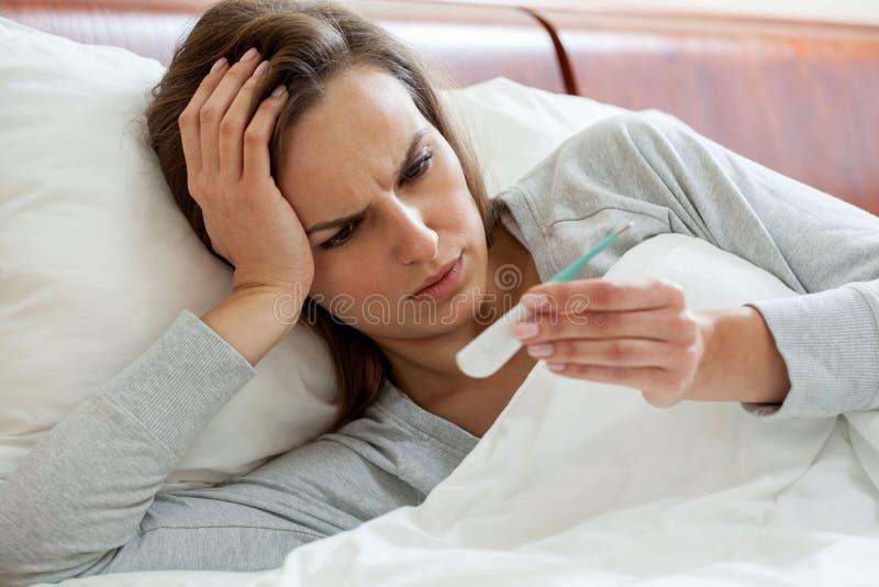 Få influensakvinnan som tar temperatur royaltyfri fotografi
