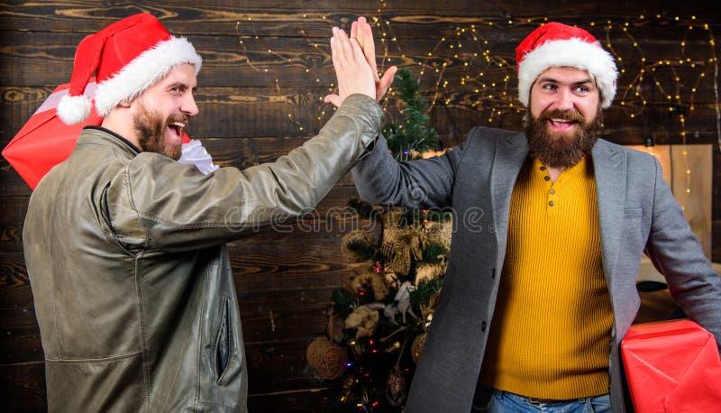 Få klar för jul Män bär askar för gåvan för den santa hatthållen Uppsökte män bär närvarande askar Leveransjulgåva royaltyfri fotografi