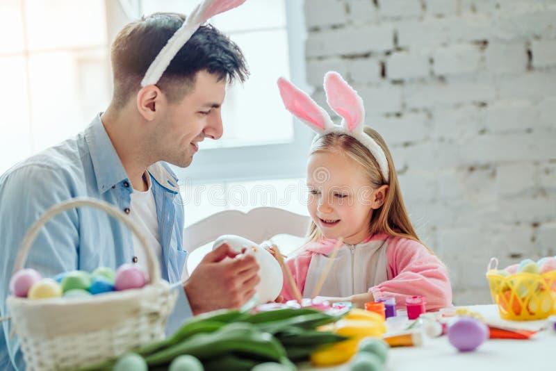 Få klart för påsk med farsan Farsan och hans lilla dotter har tillsammans gyckel, medan förbereda sig för påskferier På tabellen royaltyfri fotografi
