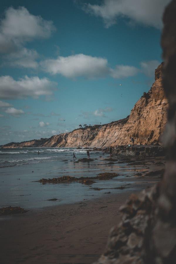 Få människor som kör på stranden med steniga berg och himmel med moln i bakgrunden arkivfoton