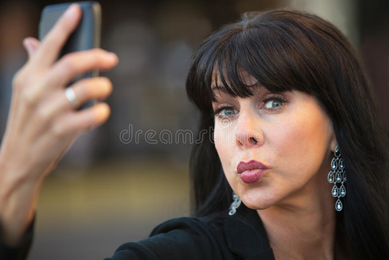 Fåfäng kvinna som tar ett självporträtt royaltyfri bild