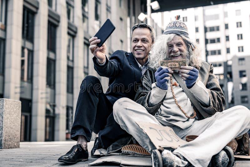 Fåfäng rikeman i dräkten som gör selfie av donationpengar royaltyfria bilder