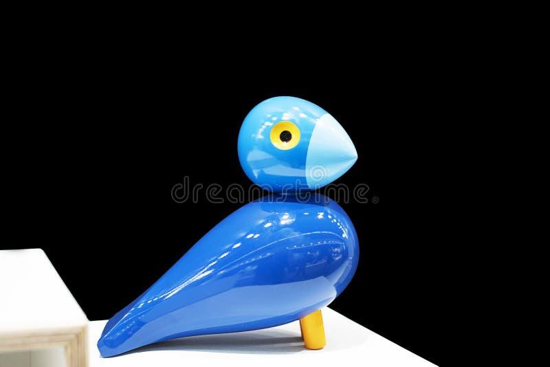 Fågel som göras av trä, snidit diagram närbild Svart bakgrund med den blåa skinande fågeln som göras av trä royaltyfri fotografi