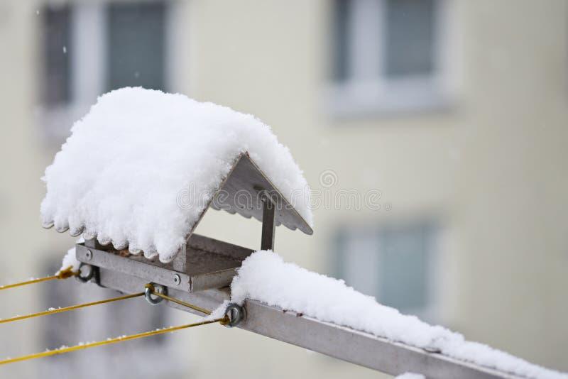Fågelförlagematare i vinter med snö Returnera på balkongen royaltyfria bilder