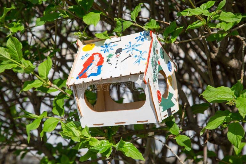 Fågelförlagematare på bakgrunden av gröna träd arkivbilder