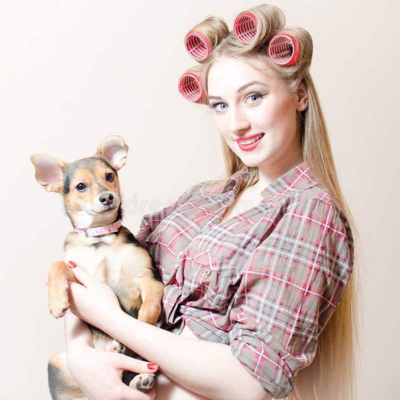Fågelunge & valp: härlig sexig blond utvikningsbrudflicka med röda kanter & hårrullar i hennes hår som rymmer lyckligt le för lit royaltyfri bild