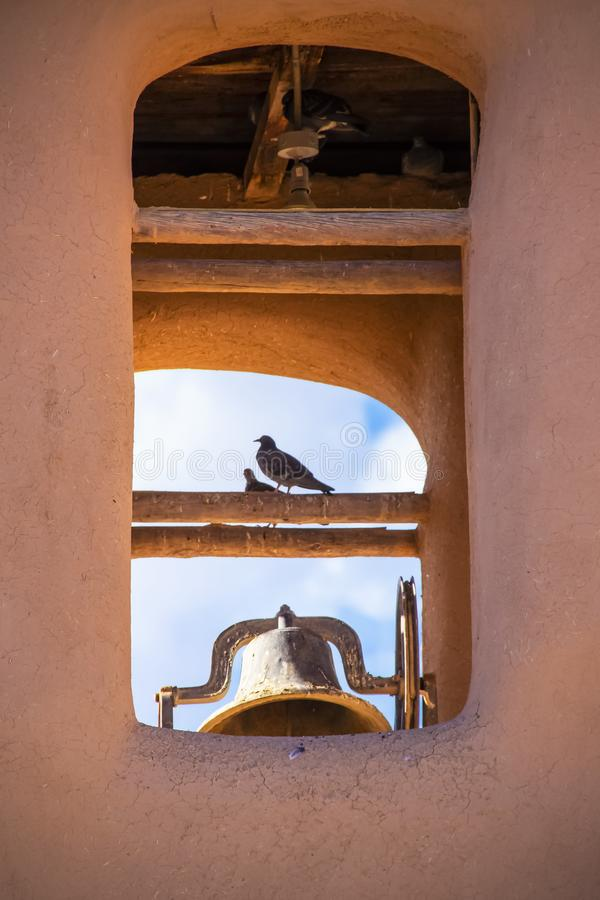 Fåglar som sätta sig i klockatorn av Adobebeskickningkyrkan i amerikanska sydväster med blå himmel som visar till och med - close royaltyfri bild