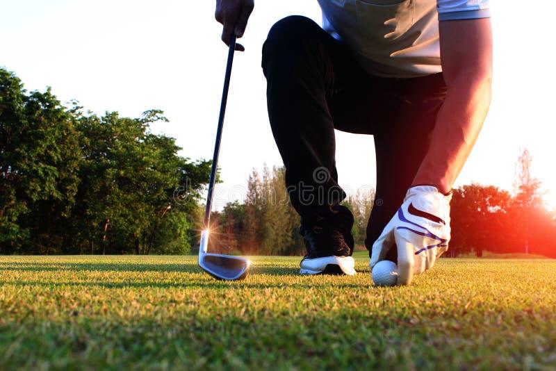 Fånga golfbollen i fältet, framme av golfarna arkivfoto