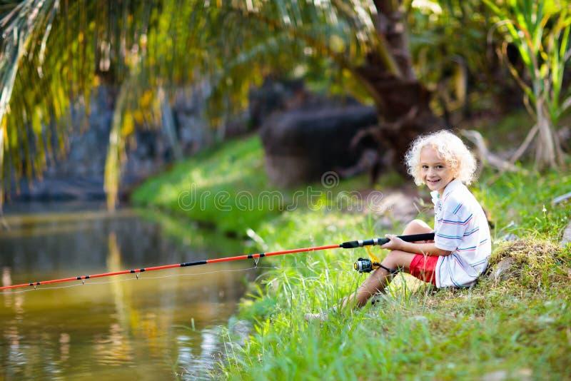 fångande sun Barn med stången som fångar fisken i floden royaltyfria bilder