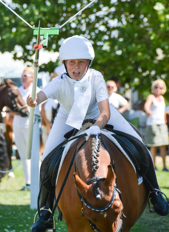 Fånget det! - ung flicka på häst på cirkelridningen arkivfoton