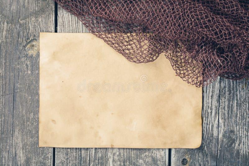 Fångstredskap - fisknät, gammalt ark av papper på en träbac royaltyfri fotografi