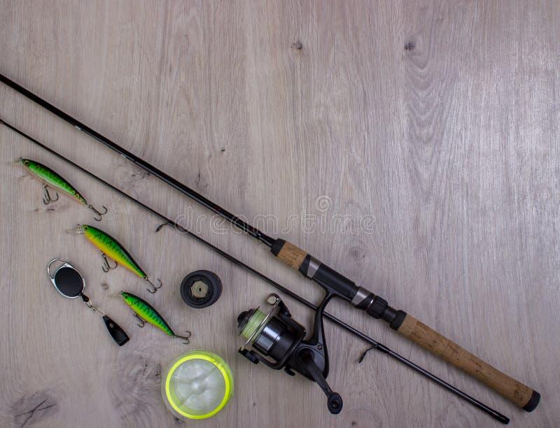 Fångstredskapet - fiskesnurr, hakar och lockar på ljus träbakgrund royaltyfri bild