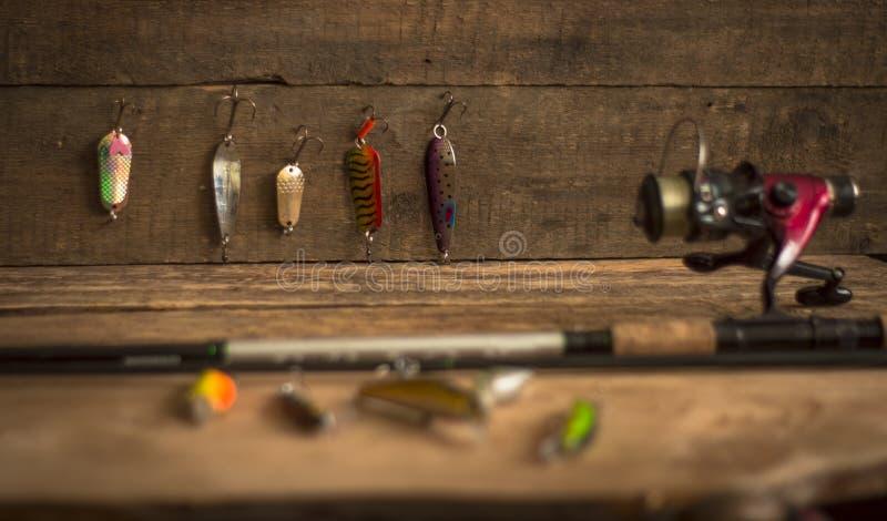 Fångstredskapet - fiskesnurr, hakar och lockar på ljus träbakgrund Top beskådar royaltyfri bild