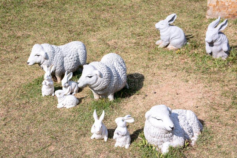 Får- och kaninstaty i trädgården royaltyfria foton