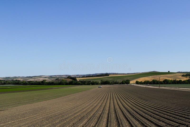 Fåror i ett plogat fält som förbereds för att plantera skördar i vår i Kalifornien Horisontalsikt i perspektiv royaltyfri fotografi