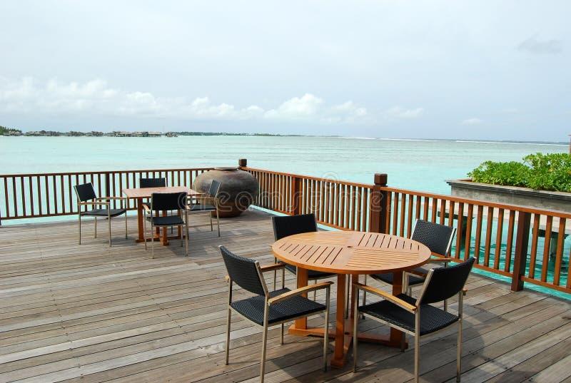 fåtöljer sätter på land tabeller för ett slags solskydd för cafevärmemiddagar under royaltyfri bild