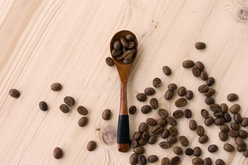 Fèves de café rôties dans une cuillère en bois sur une table image stock