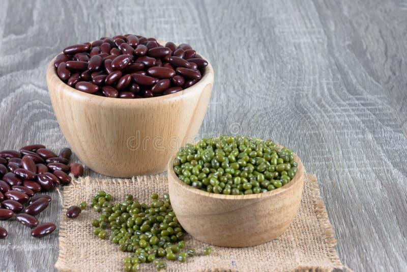 Fèves de mung et haricot nain rouge dans l'endroit de cuvette sur la table en bois photos stock
