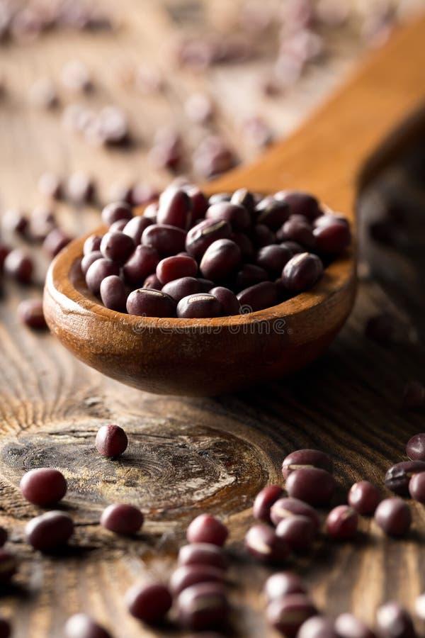 Fèves de mung rouges crues, crues, sèches d'adzuki dans la cuillère en bois sur le fond en bois rustique de table photo stock