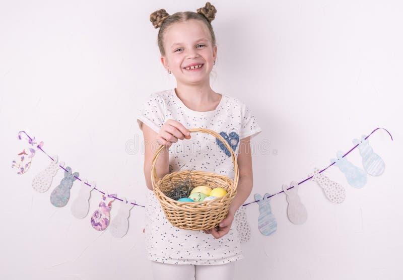 Félicitations sur Joyeuses Pâques : la fille tient un panier avec les oeufs peints par le mur blanc photographie stock