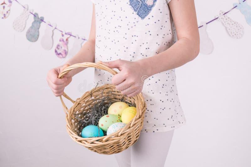 Félicitations sur Joyeuses Pâques : la fille tient un panier avec les oeufs peints par le mur blanc photo libre de droits