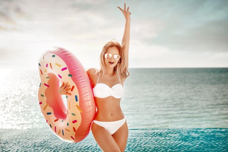 Férias de verão Apreciando a mulher do bronzeado no biquini branco com o colchão da filhós perto do oceano foto de stock