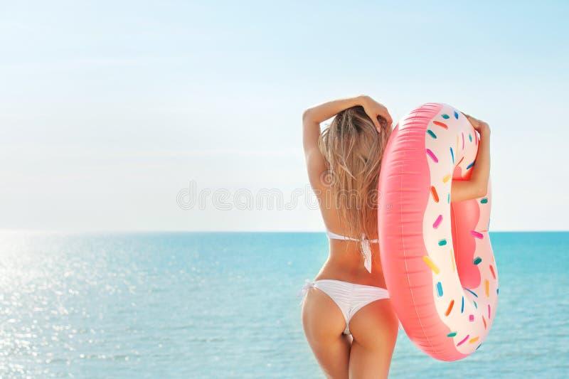 Férias de verão Apreciando a mulher do bronzeado no biquini branco com o colchão da filhós perto da piscina fotos de stock royalty free