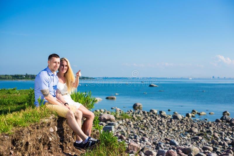 Férias de verão e conceito do curso - par feliz na praia rochosa foto de stock royalty free