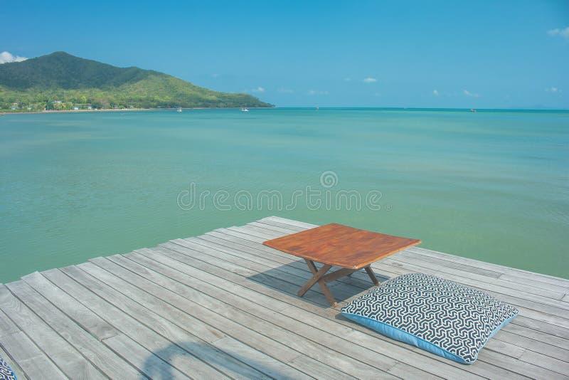 Férias de verão e conceito do feriado: Viagem do verão no mar, no descanso e na tabela de madeira no terraço exterior para o abra foto de stock