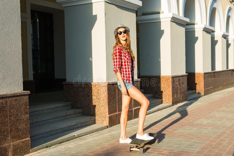 Férias de verão, esporte extremo e conceito dos povos - menina feliz que monta o skate moderno na rua da cidade imagens de stock