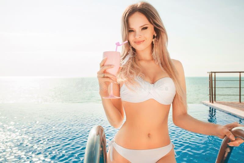Férias de verão Mulher no biquini no colchão inflável na piscina dos TERMAS com coctail imagens de stock