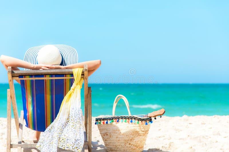 Férias de verão Mulher saudável do estilo de vida asiático que relaxa e feliz na cadeira de praia com suco do coco do cocktail no foto de stock