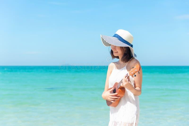 Férias de verão Mulheres asiáticas de cheiro que relaxam e que jogam uma uquelele na praia, tão feliz e luxuoso no verão do feria fotos de stock
