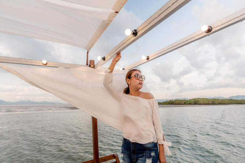 Férias de verão, mulheres felizes que relaxam no telhado do iate no por do sol Mar de Andaman Tailândia imagem de stock royalty free