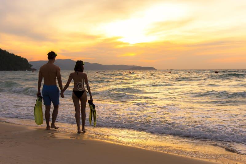 Férias de verão Pares que andam guardando as mãos em tropical no tempo do por do sol da praia no feriado após a nadada do tubo de imagem de stock royalty free