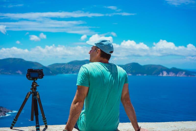 Férias de verão que visitam Grécia Fotógrafo masculino que aprecia para capturar o cloudscape, o litoral e o mar do lapso de temp fotografia de stock