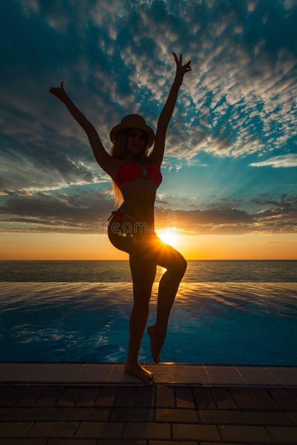 Férias de verão Silhueta da mulher da dança da beleza no por do sol perto da associação com vista para o mar foto de stock