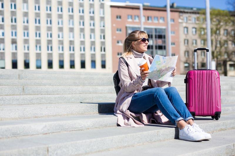 Férias de verão, turismo e conceito do curso - jovem mulher com mapa e mala de viagem do turista - espaço da cópia sobre escadas fotografia de stock royalty free