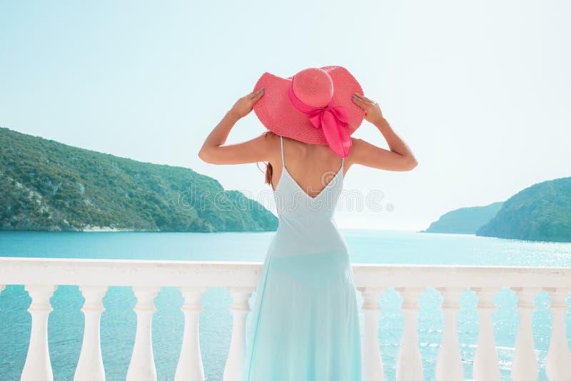 Férias do curso de Europa Grécia Mulher que olha a opinião do mar Vestido vestindo do estilo de vida extravagante vivo elegante d fotografia de stock