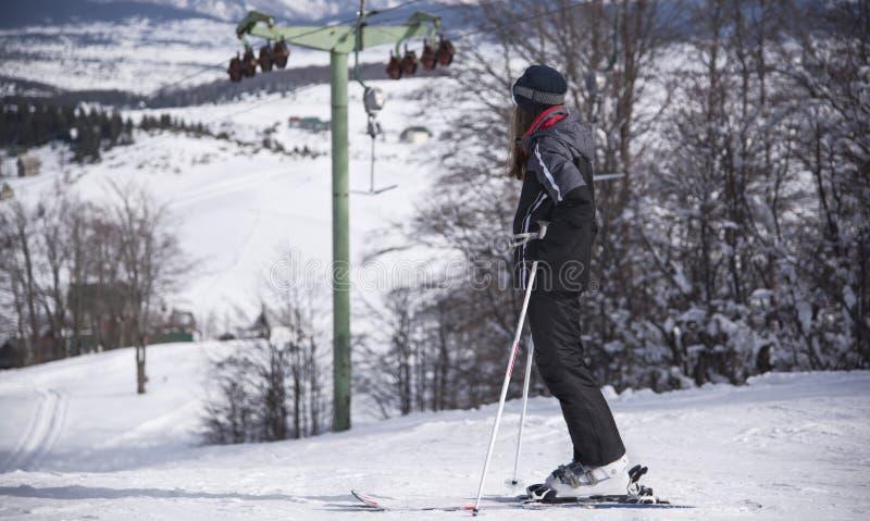Férias do inverno, esportes de inverno, menina que aprecia a vista, esqui em declive, olhando a trilha, Montenegro, Zabljak, 2019 imagens de stock